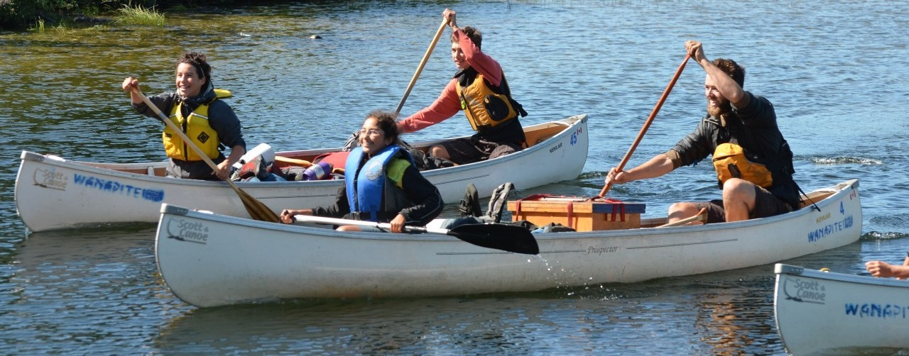 campers and leaders paddling canoes