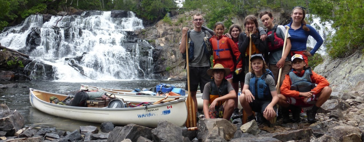 group in front of waterfall