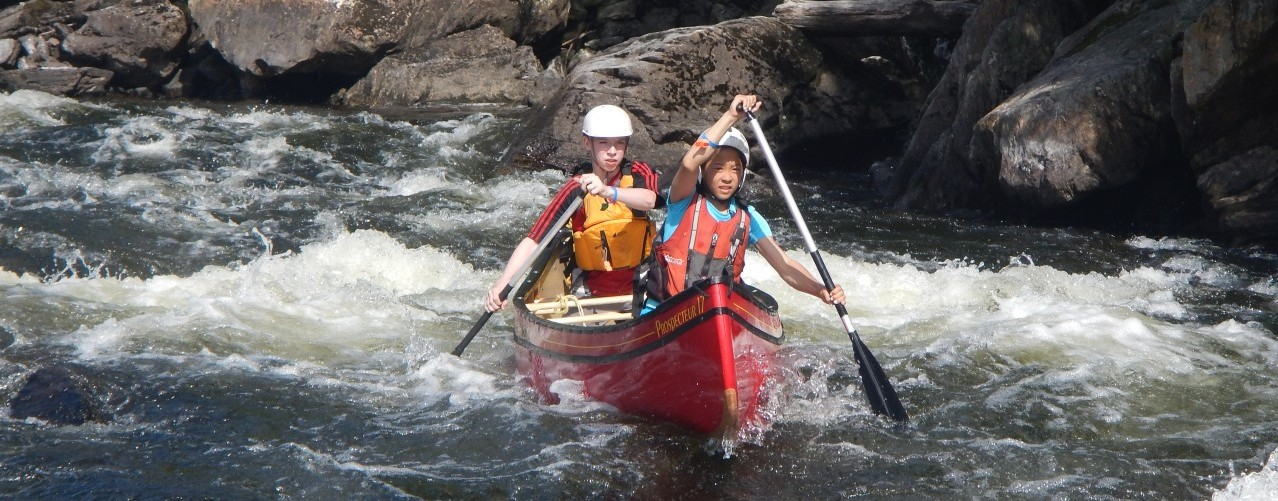 campers paddle whitewater